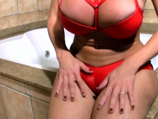 Mature shemale in sexy red outfit strokes bigtits and t-dick