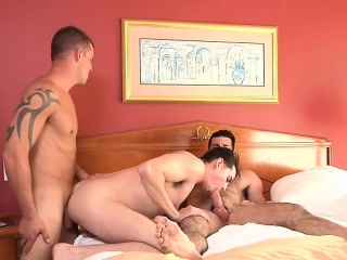 three horny gay guys are taking turns on a rock hard schlong
