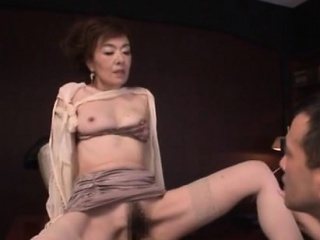 Beautiful older playgirl jerks off a hard cock on her tits